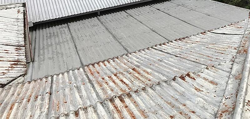 Rusted and flaking roof sheets on old roof