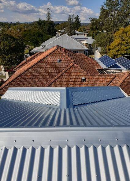 New metal roof with old tile roof in background