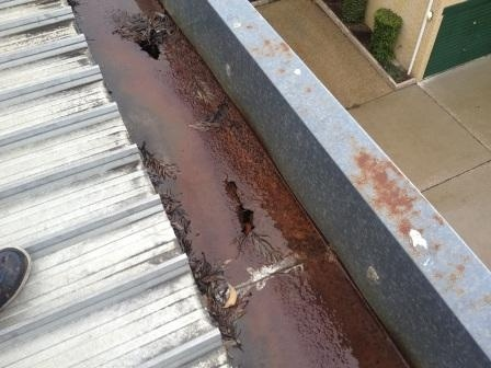 Severely rusted gutter with holes