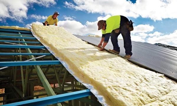 Roofers installing anti-condensation blanket