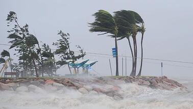 High winds drive surf onto land, trees blowing
