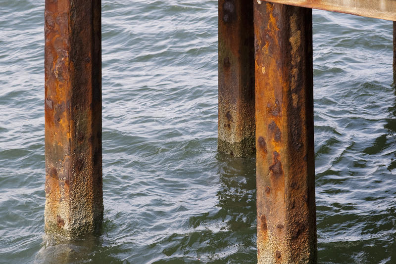 Rusted pier supports in ocean