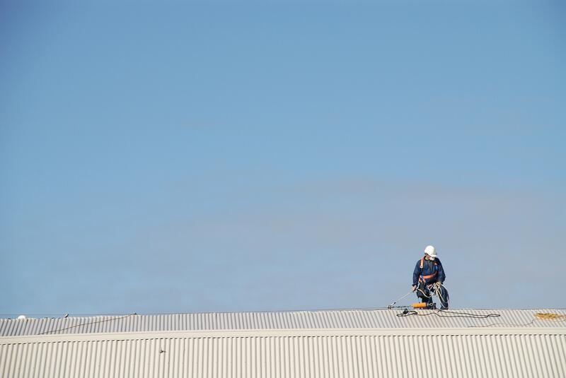 Roofer using harness on roof