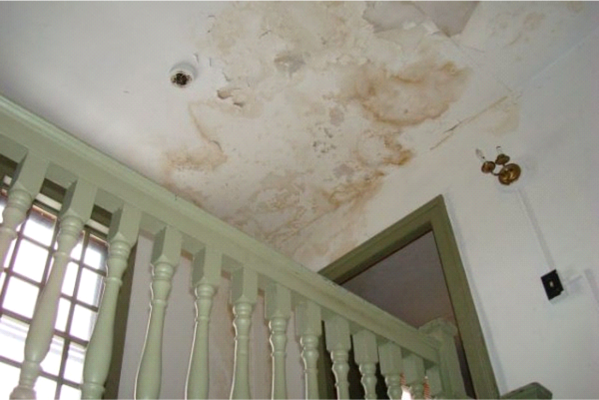 Water damage to ceiling inside home: discolouration, flaking paint and sheet particles