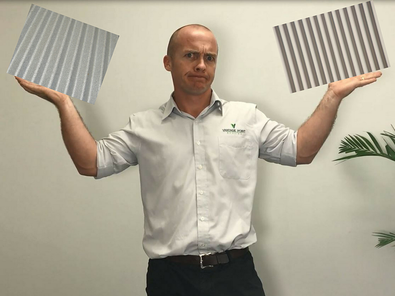 Video still: Our director Luke holding sheets of Zincalume and Colorbond roof sheeting looks puzzled